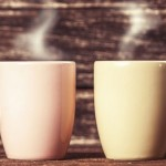 Two cups of coffee on wooden table.