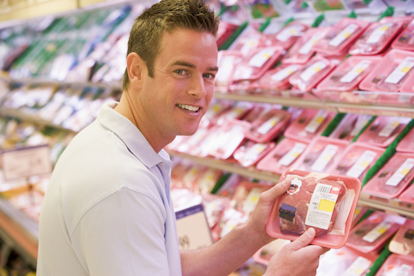 Man buying fresh meat from supermarket counter