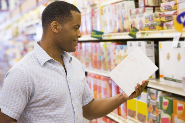 Man shopping in supermarket checking contents of packet