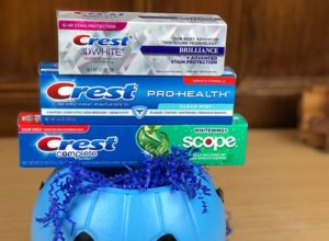 Crest Halloween image with Crest toothpaste stacked on top of a blue pumpkin bucket with blue streamers inside the bucket.